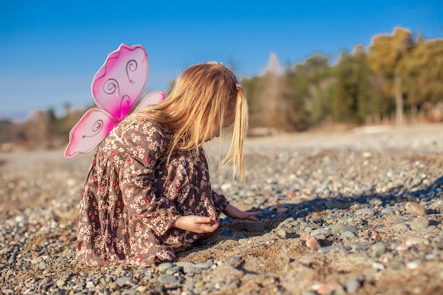 Adorable little girl playing on the beach in a winter sunny day