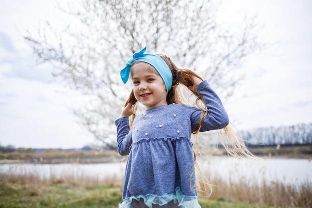 사랑스러운 어린 소녀가 부활절 달걀 사냥에 꽃이 만발한 사과나무 정원에서 뛰놀고 웃고 있습니다. 벚꽃과 봄 과일 과수원에서 아이입니다.