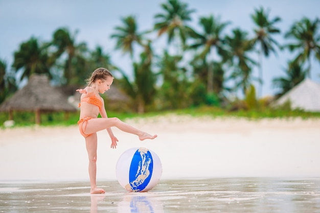 Adorable little girl playing with ball on beach, kids summer sport outdoors