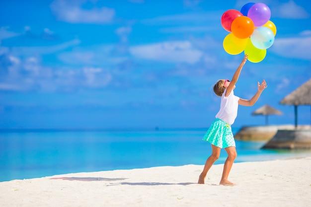해변에서 풍선을 가지고 노는 사랑스러운 작은 소녀