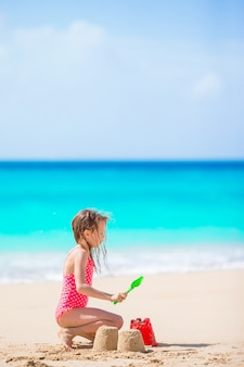 Adorable little girl playing with beach toys on white tropial beach