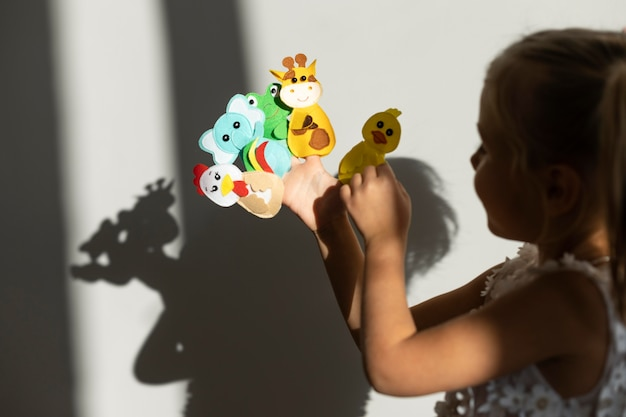 Очаровательная маленькая девочка играет со своими куклами дома