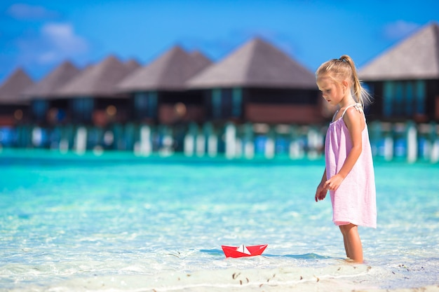 Adorable little girl playing with paper boat in turquoise sea