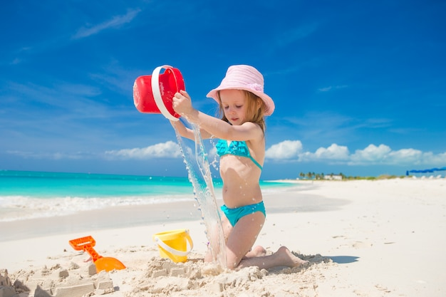 Adorable little girl playing with sand on a perfect tropical beach