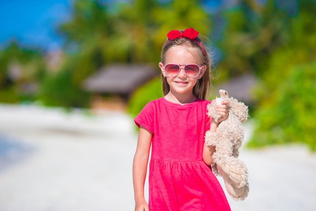 Adorable little girl playing with toy during beach vacation