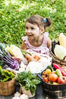 愛らしい少女が芝生の上でさまざまな野菜で遊ぶ