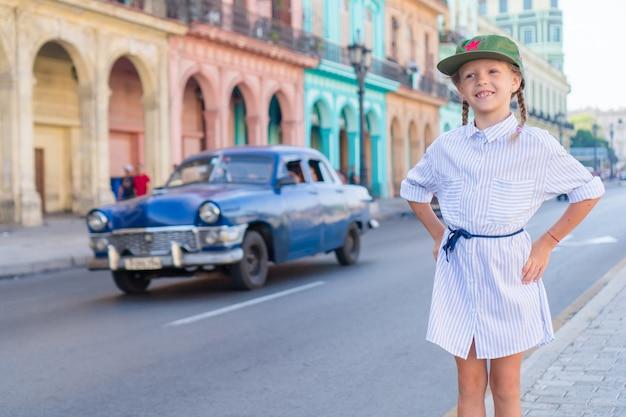 Adorable little girl in popular area in old havana, cuba. portrait of kid, vintage classic american car
