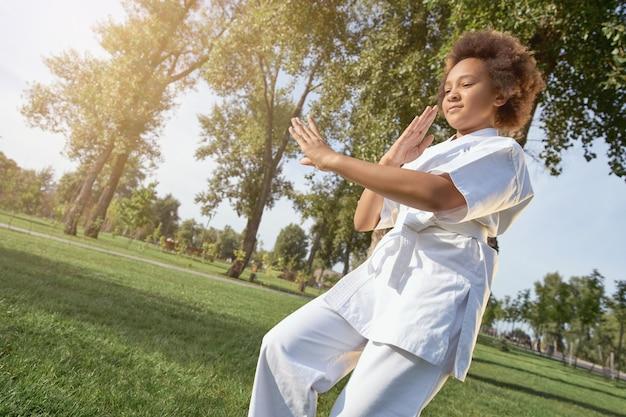 屋外で武道を練習している愛らしい少女