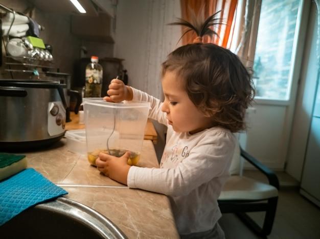 Очаровательная маленькая девочка готовит еду малышу на кухне, смешивая ингредиенты в миске