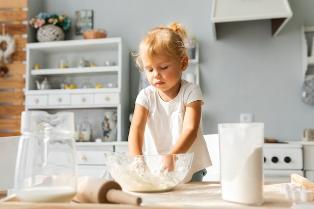 Adorable little girl preparing dough
