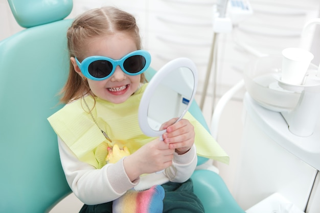 Adorable little girl in protective glasses checking her teeth in the mirror at dental clinic