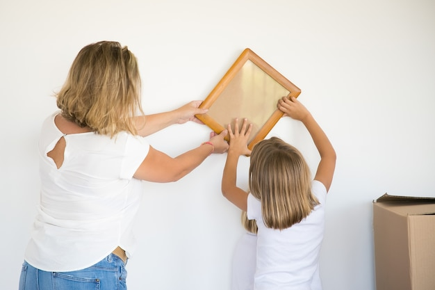 Adorable little girl putting photo frame on white wall with help of mom