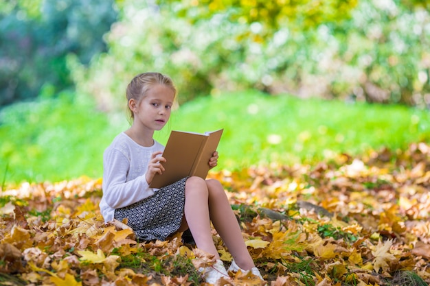 Adorable little girl reading a book in beautiful autumn park
