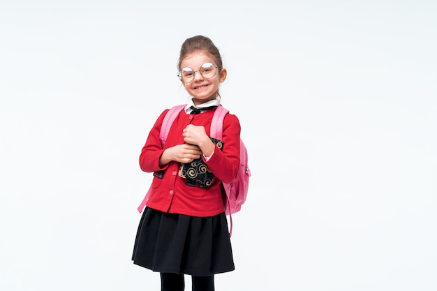 Adorable little girl in red school jacket, black dress, backpack and rounded glasses hugs a book tightly and smiles