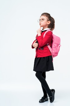 Adorable little girl in red school jacket, black dress, backpack and rounded glasses hugs a book