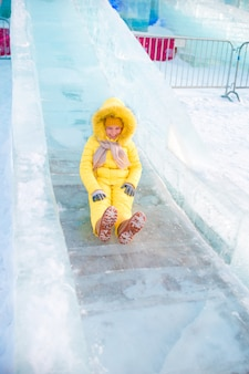 Adorable little girl riding on an ice hill outdoors