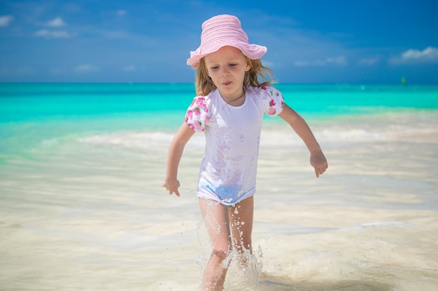 Adorable little girl runing in shallow water at exotic beach