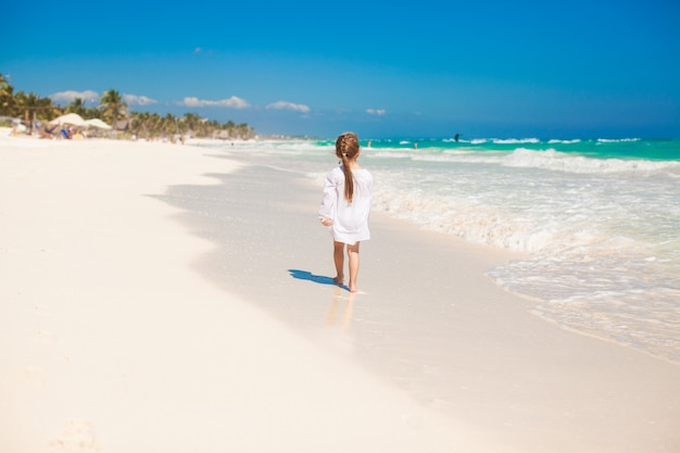 Adorable little girl running on exotic white beach at sunny day