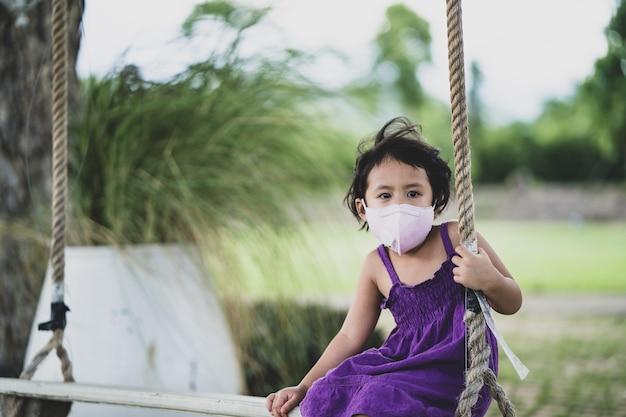 公園のブランコに座って健康的なフェイスマスクを身に着けている愛らしい少女の悲しい表情