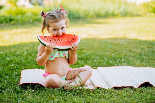 Adorable little girl sit on the grass and eat red ripe watermelon. childhood, immunity, happiness, healthy snack