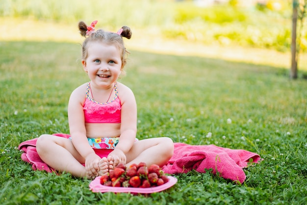 Adorable little girl sit on the grass with plate of fresh ripe strawberries and smile. childhood, immunity, happiness.