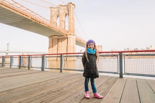 Очаровательная маленькая девочка сидит на бруклинском мосту в нью-йорке