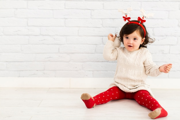 Adorable little girl sitting next to brick wall