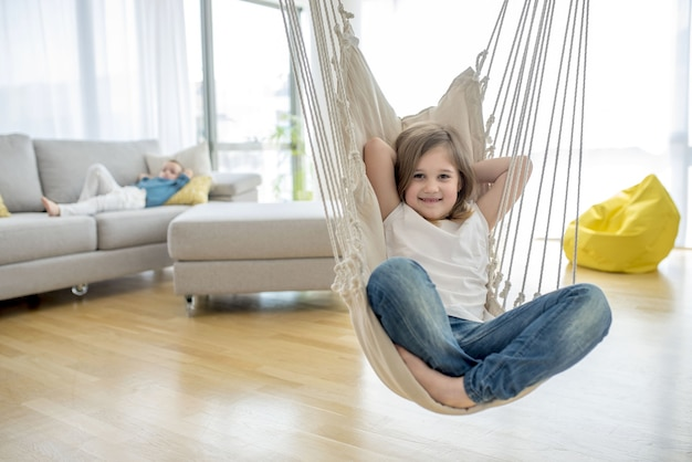 Adorable little girl sitting on the hammock in the house