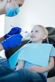 Очаровательная маленькая девочка сидит в кресле стоматолога и собирается пройти обследование полости рта, проводимое стоматологом-женщиной