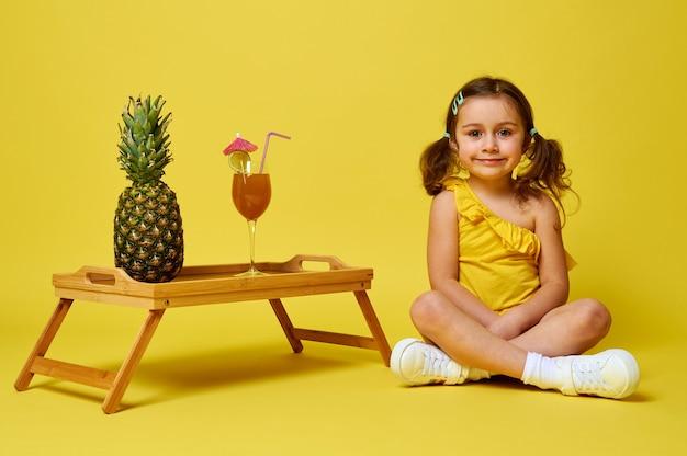 Очаровательная маленькая девочка сидит на желтом фоне возле сервировочного бамбукового подноса