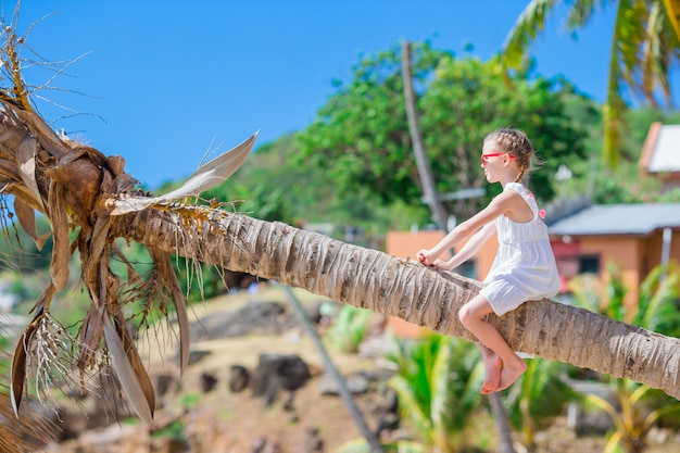 Adorable little girl sitting on palm tree during summer vacation on white beach