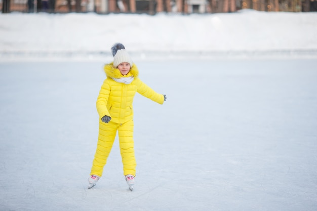 Adorable little girl skating on the ice rink outdoors at warm winter day