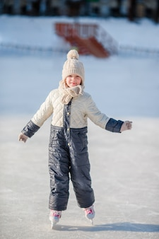 Adorable little girl skating on the ice rink outdoors.
