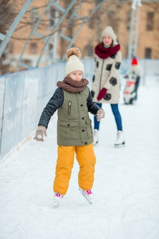 Adorable little girl skating on the ice rink outdoors
