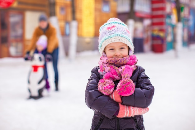 Adorable little girl on skating rink with father and sister