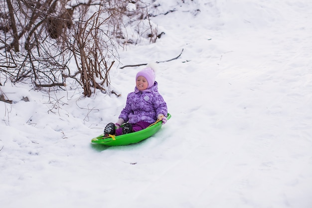 Adorable little girl sledding in snowy forest