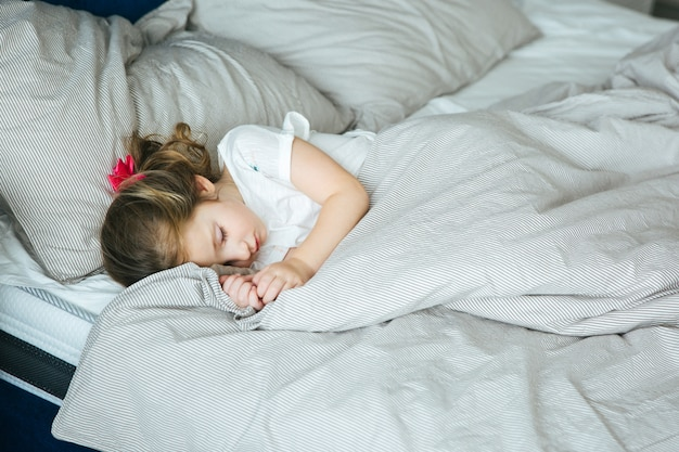 Adorable little girl sleeping in the bed in pajamas under the blanket at home, calm and peaceful