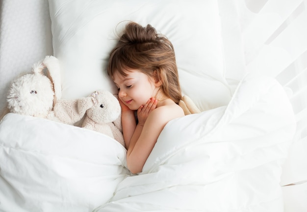 Adorable little girl sleeping sweetly in a white bed with rabbit toys lying near. top view.
