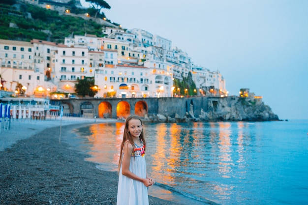 Adorable little girl on sunset in amalfi town in italy