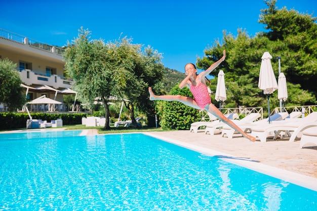 Очаровательная маленькая девочка плавает в открытом бассейне