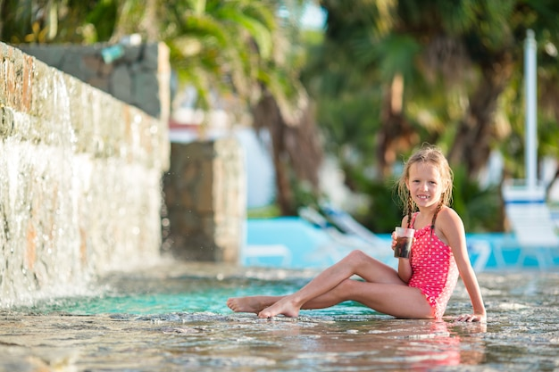 Adorable little girl in swimming pool outdoors