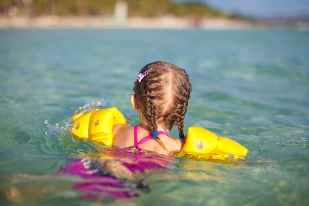 Adorable little girl swimming in the sea on tropical beach vacation