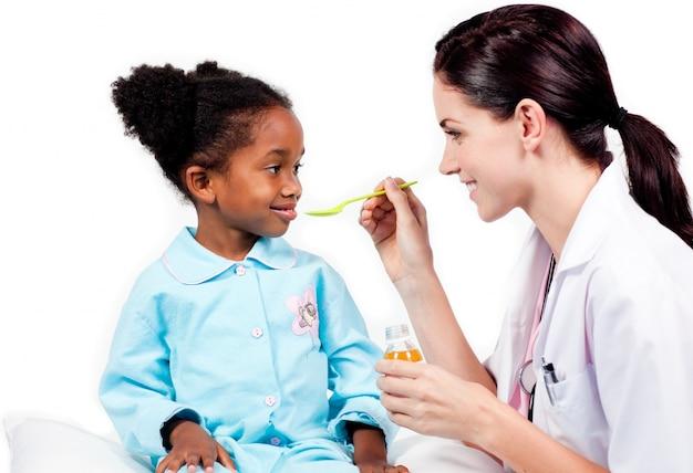Adorable little girl taking medicine