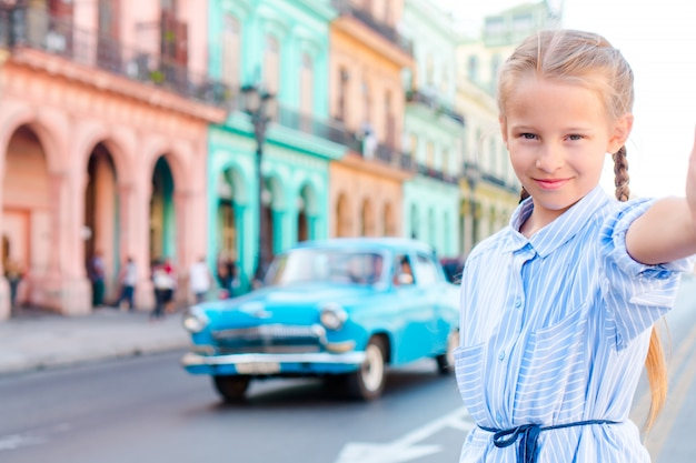 Adorable little girl taking selfie in popular area in old havana, cuba. portrait of kid outdoors on a street of havana