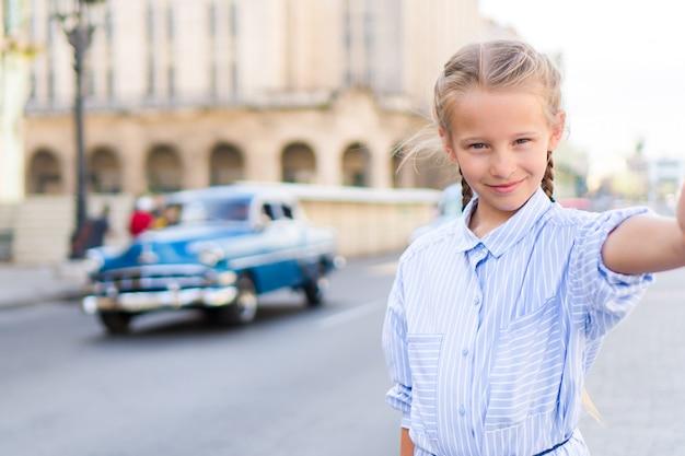 Adorable little girl taking selfie in popular area in old havana, cuba. portrait of kid outdoors on a street of havana