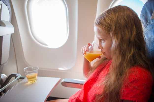 Adorable little girl traveling by an airplane. kid drinking orange juice sitting near aircraft window