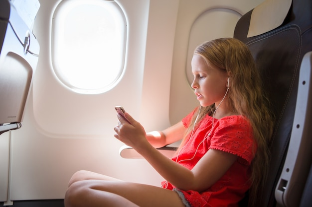 Adorable little girl traveling by an airplane. kid listening music sitting near aircraft window