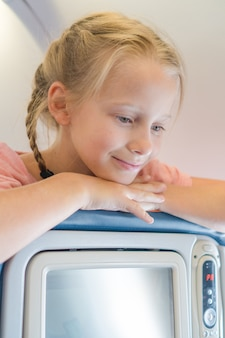 Adorable little girl traveling by an airplane and smiling