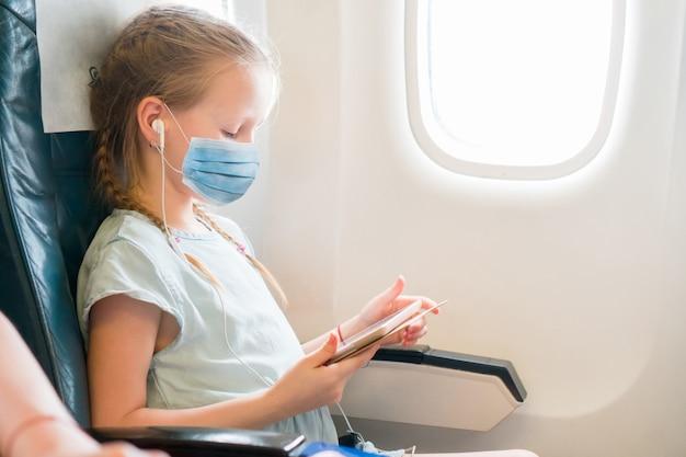 飛行機で旅行するかわいい女の子。