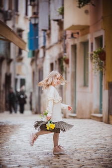 Adorable little girl in trend clothes dansing in old town in sunny spring day